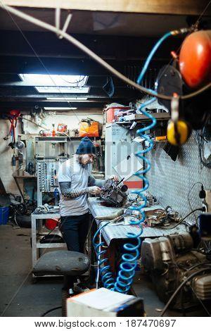 Hipster repairing engine of motor-bike