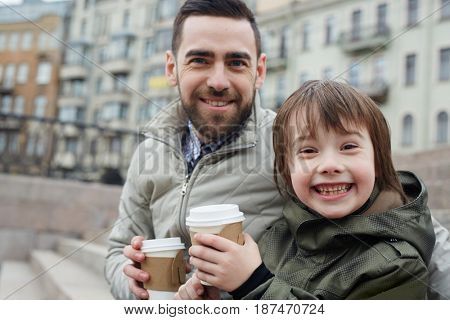 Boy and his father with drinks looking at camera outdoors