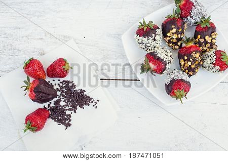 Variety of strawberries covered with a dark chocolate with nuts pistachios and coconut on the white wooden table. Homemade choco dipped berry. Gourmet summer dessert. Top view.