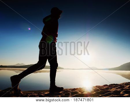 Silhouette Of Active Man Exercising  And Stretching On The Lake Beach At Sunrise.