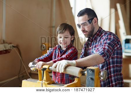 Carpenter in protective eyeglasses and his son processing wooden workpiece in workshop