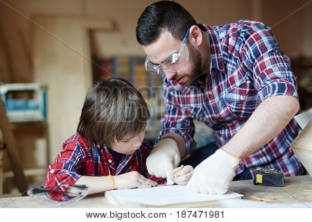 Little boy drawing line on wooden workpiece while his father helping him
