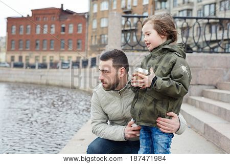 Man embracing his son while standing by river in urban environment