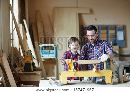 Young man showing his son how to process wooden planks