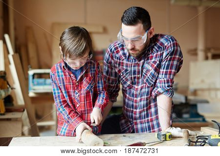 Creative man and little boy wood crafting together