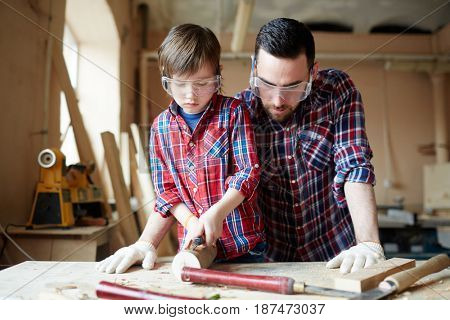 Youthful kid with chisel carving wooden workpiece with his father near by