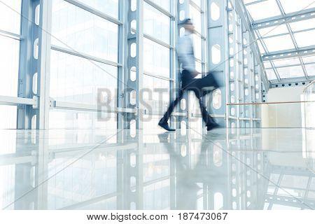 Hurrying businessman walking down modern office center