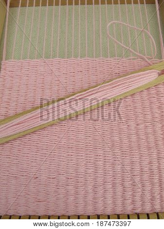 Weaving with weaving frame and pink wool