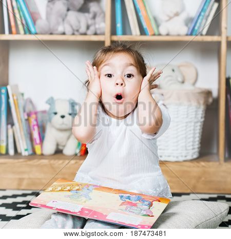 Cute emotional little girl reading book and surprised.