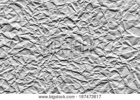 the old crumpled sheet of paper of silvery color for the abstract textured background and for wallpaper