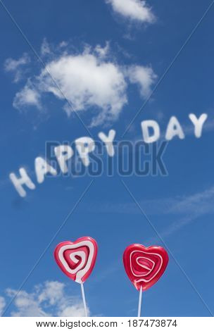 The word Happy Day in the blue cloudy sky and two lollipop