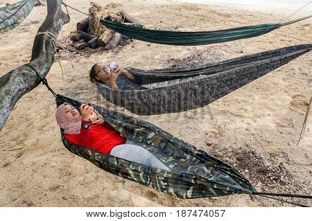 Labuan,Malaysia-Feb 19,2017:Young people playing smartphones while enjoying the hammock on tropical beach in Papan island,Labuan,Malaysia.
