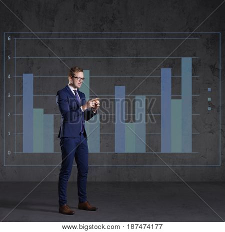 Businessman with smartphone standing on a column diagram background. Business, office, career, job concept.