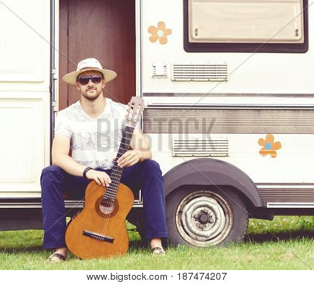 Young, handsome, bearded hipster playing guitar outdoors at summer. Holiday, journey, vacation concept.