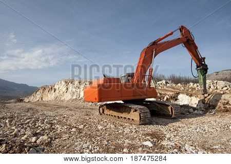 Orange backhoe drilling stone soil on construction of road