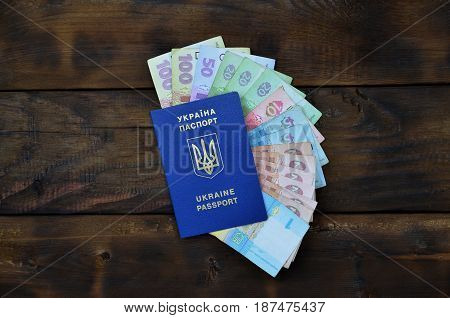 A Photograph Of A Ukrainian Passport And A Certain Amount Of Ukrainian Money On A Wooden Surface. Th