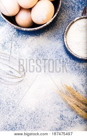 Fresh Eggs In A Bowl, Eggbeater, Wheat On Flour Background. Top View. Copy Space.