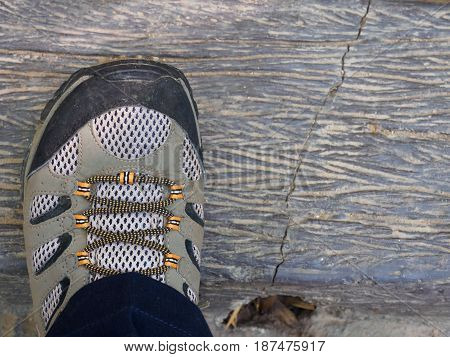 Hiking boots on timber woods pavement concept for leg in boots on trekking trip.