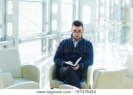 Serious employer with notebook sitting in armchair