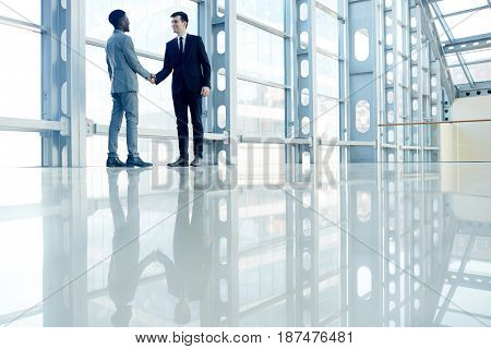 Two businessmen handshaking in office-center