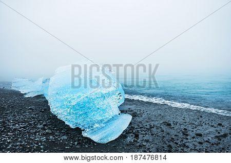 Blue Ice On The Black Volcanic Beach.