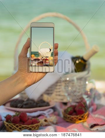 Photo of a summer picnic on the beach on a smartphone. Selective focus.