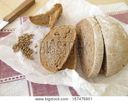 Loaf of farmhouse bread with coriander on paper
