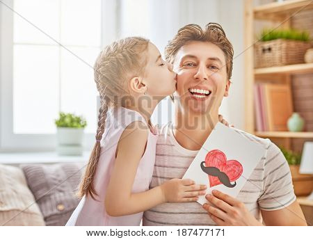 Happy father's day! Child daughter congratulates dad and gives him postcard. Daddy and girl, kissing, smiling and hugging. Family holiday and togetherness.