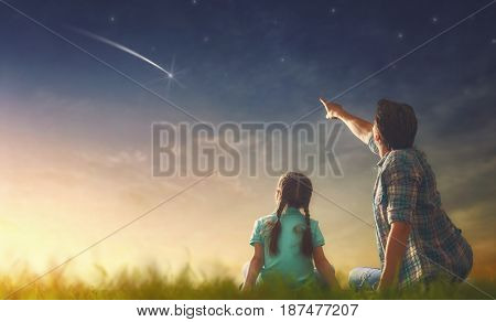 Father and his daughter are looking at falling star.