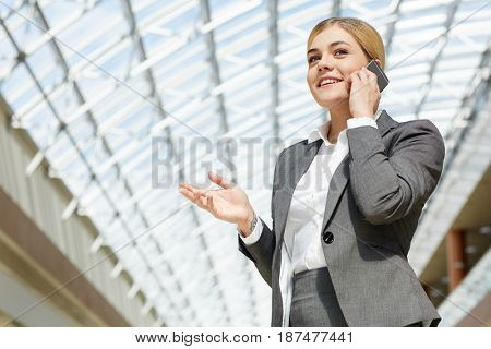 Young woman in formalwear speaking to client by cellphone