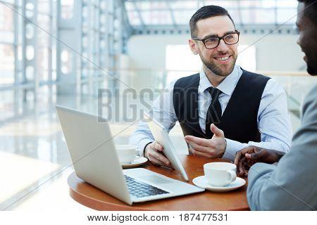 Happy economist showing online data to colleague