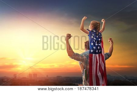 Patriotic holiday. Happy family, father and his daughter child girl with American flag outdoors on background sunset cityscape. USA celebrate 4th of July.