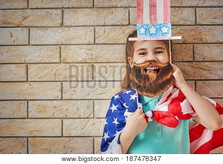 Patriotic holiday. Happy kid, cute little child girl with American flag in the room indoors. USA celebrate 4th of July.