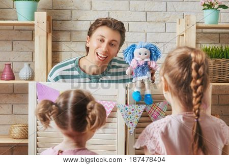 Happy loving family. Father and his daughter in kids room. Funny dad and lovely child having fun and playing performance in the puppet theater indoors.
