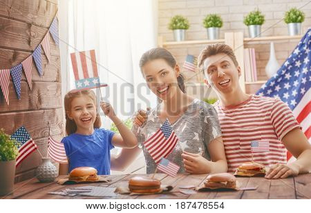 Patriotic holiday. Mother, father and daughter are doing burgers. Happy family are celebrate 4th of July. Cute little child girl with American flag in the room at home.