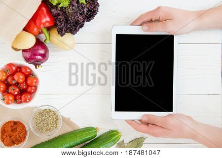 Close-up Partial View Of Person Using Digital Tablet With Blank Screen While Cooking And Fresh Ingre