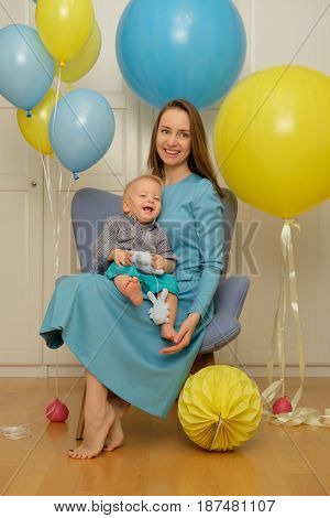 One year old baby boy first birthday. Toddler child with mother sitting in chair and having fun with balloons