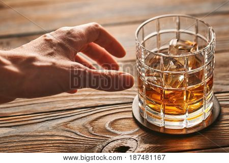 Man's hand reaching to glass of whiskey with ice cubes on rustic wooden table. Alcoholism concept.
