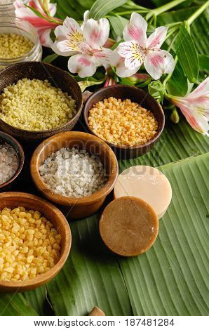 wooden bowl of color sea salt with , ,massage oil and orchid , on banana leaf