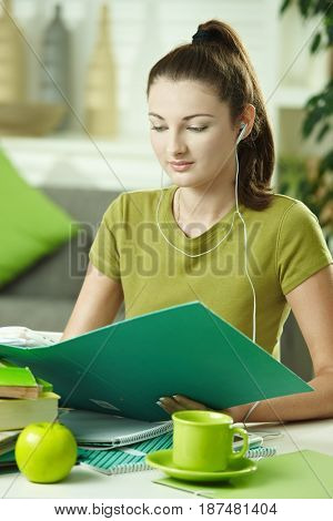 Teen girl learning at desk at home doing homework, looking down at workbook.