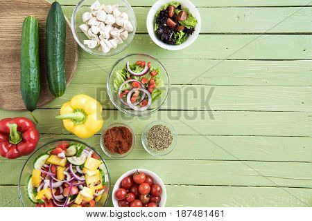 Top View Of Fresh Raw Vegetables And Salads In Bowls On Wooden Table