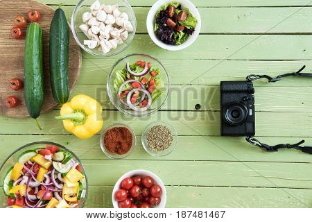 Top View Of Fresh Raw Vegetables And Salads In Bowls And Camera On Wooden Table