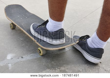 Skater and skateboard legs detail. Lifestyle urban background. Outdoors