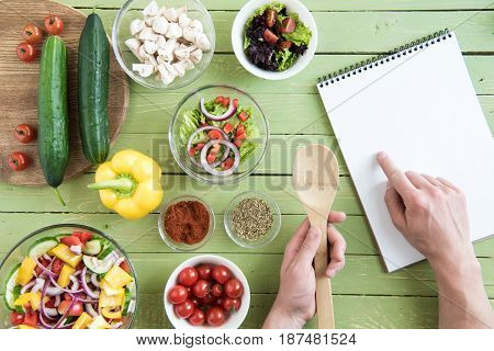 Close-up Partial View Of Person Holding Wooden Spoon And Pointing At Recipe In Cookbook While Cookin