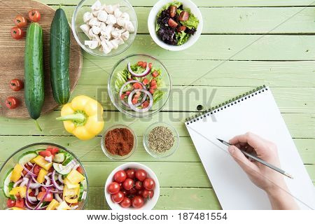 Close-up Partial View Of Person Holding Pencil And Writing Recipe In Cookbook While Cooking