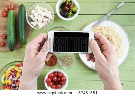 Close-up Partial View Of Person Holding Smartphone With Blank Screen And Photographing Spaghetti And