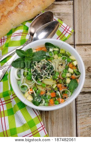 Light refreshing soup of carrots zucchini potatoes leeks peas pesto parmesan and mint leaves. View from above.