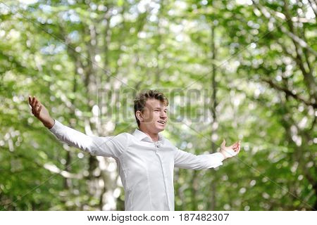 Happy young man with open wide arms celebrating success