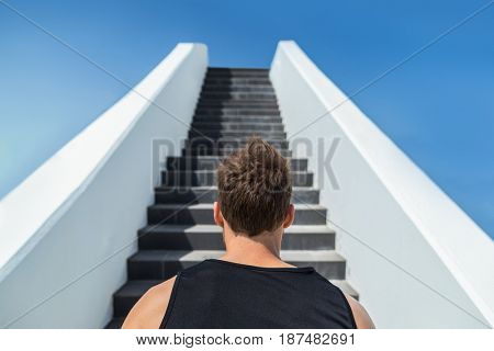 Fitness man looking ahead at stairs climbing challenge. Runner going up running staircase for cardio goal doing weight loss choice in healthy lifestyle. Man choosing difficult path.