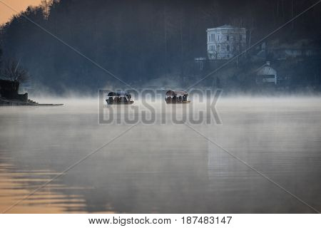 Two pletna boats in Slovenia floaing in mist towards an island inside the lake.